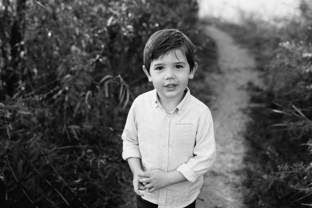 4 year old boy with dark hair and eyes wearing button down shirt standing on path looking up at camera - Markham In-Home Photos