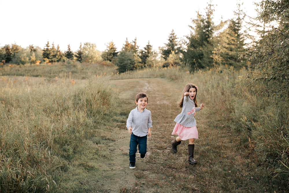 4 year old boy and 5 year old girl with dark hair running down path in grassy field smiling, sister's arms outstretched towards camera - Newmarket Lifestyle Photos
