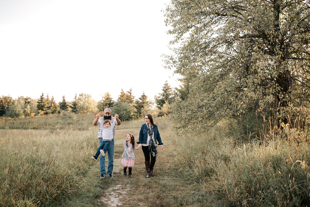 family of 4 holding hands, walking down path in grassy field, dad swinging son by both arms, mother and daughter laughing at them - York Region Lifestyle Photos
