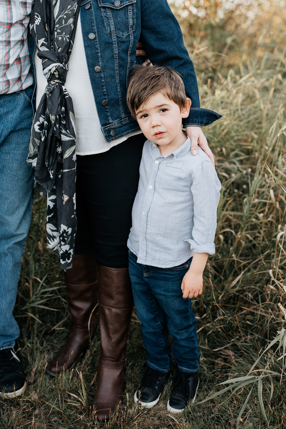 portrait of 4 year old boy with dark hair and brown eyes wearing blue button down shirt and jeans standing next to mom, whose hand is resting on his shoulder, close up of child - GTA Lifestyle Photography