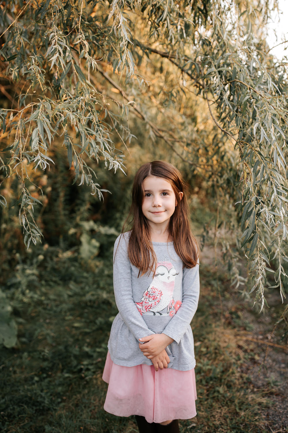 5 year old girl with dark hair and brown eyes standing under willow tree wearing pink skirt and grey top, hands folded in front of her looking and smiling softly at camera -Markham In-Home Photography