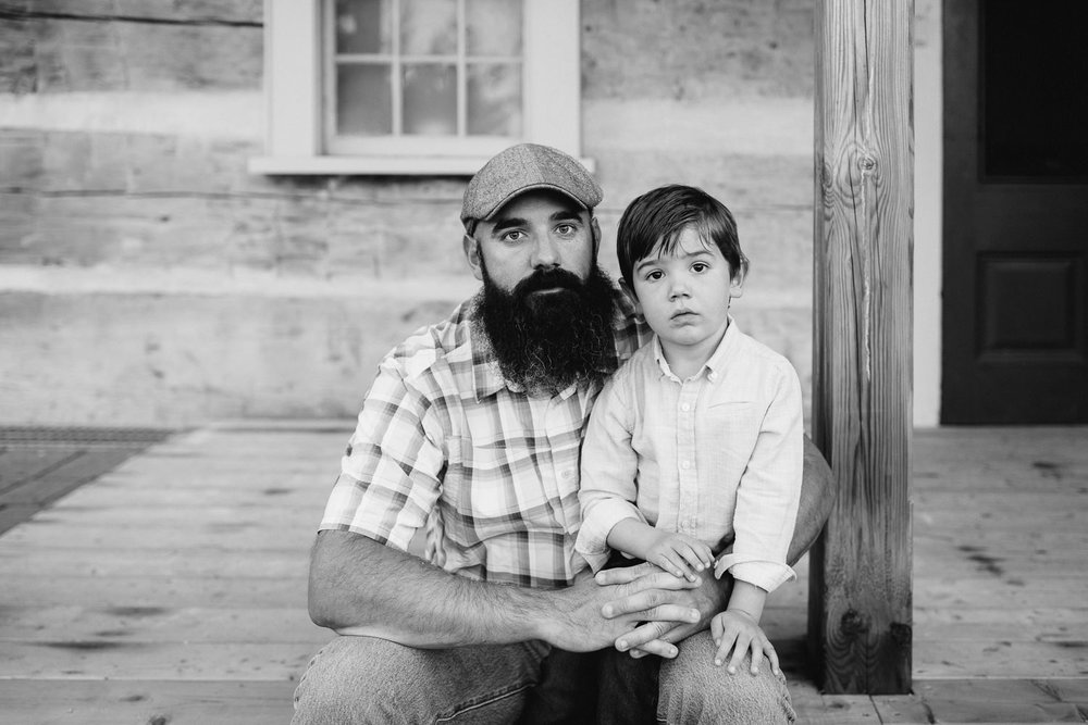 father with long dark beard sitting on wood porch step with 4 year old boy in his lap, dad's arms wrapped around son, both looking seriously at camera -Barrie In-Home Photos