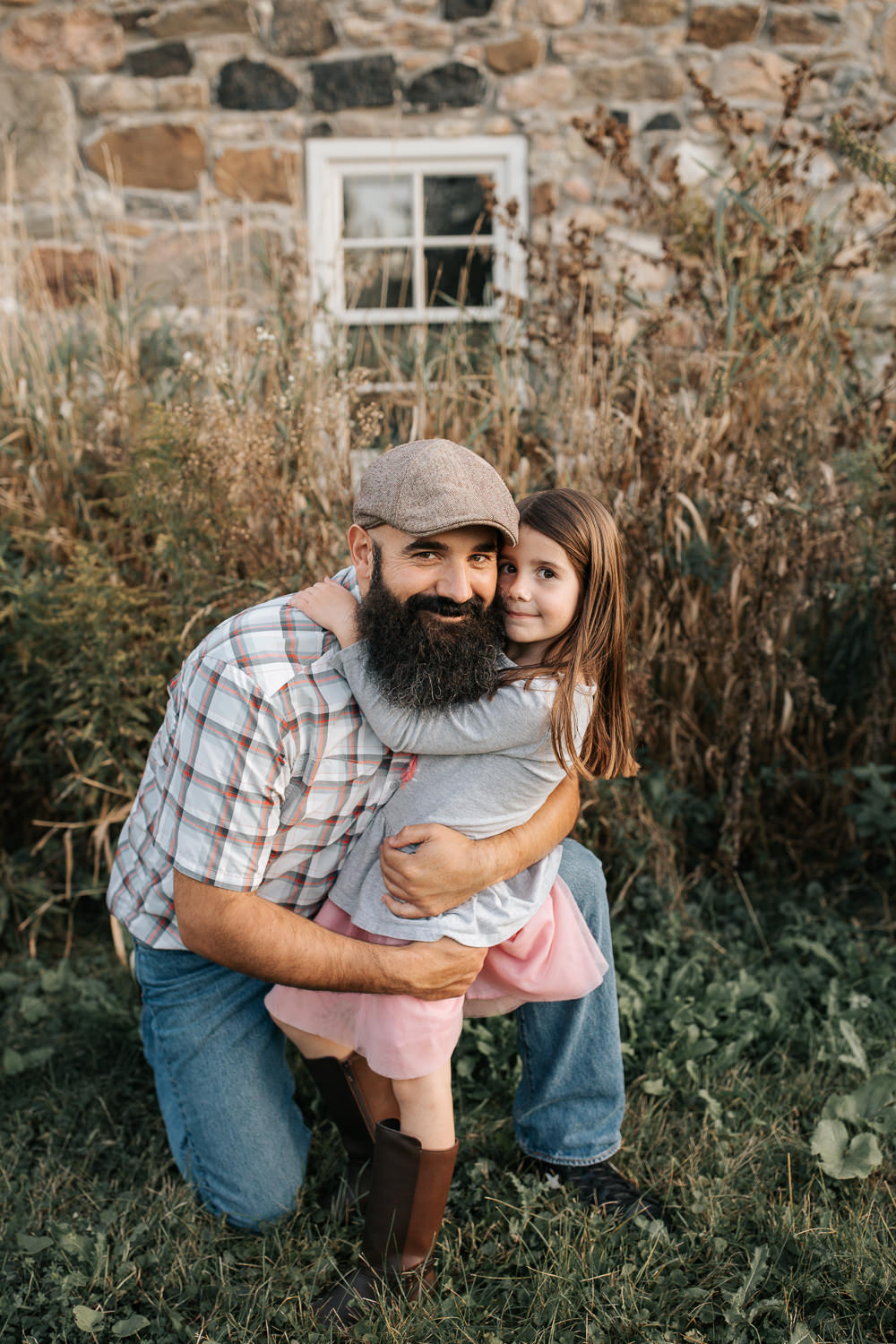 father bending down on one knee in front of old stone house as 5 year old girl hugs him around the neck, dad's arms around daughter, both smiling at camera  - Markham Lifestyle Photos