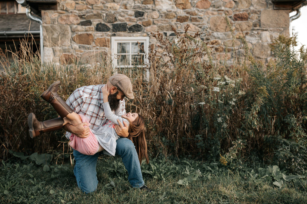 father bending down on one knee in front of old stone house, 5 year old girl swept up in his arms, daughter's hand around dad's neck - GTA Lifestyle Photos