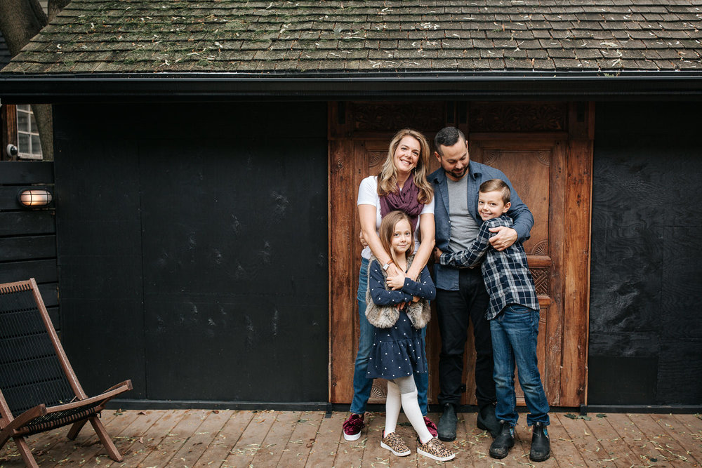family of 4 standing on front of dark home with old doors, mom's arms around 7 year old girl's shoulders, both smiling at camera, 9 year old boy hugging dad - Newmarket Lifestyle Photography