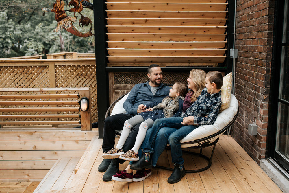 family of 4 sitting and snuggling on outdoor couch, 7 year old girl sitting in dad's lap holding his hand, 9 year old boy sitting in mom's, laughing and smiling - York Region Lifestyle Photography