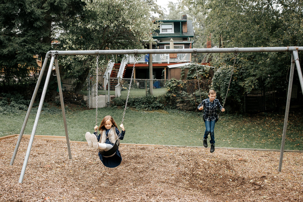 9 year old boy and 7 year old girl at outdoor park in the city swinging on swing set, focused looks on their faces - Barrie In-Home Photography