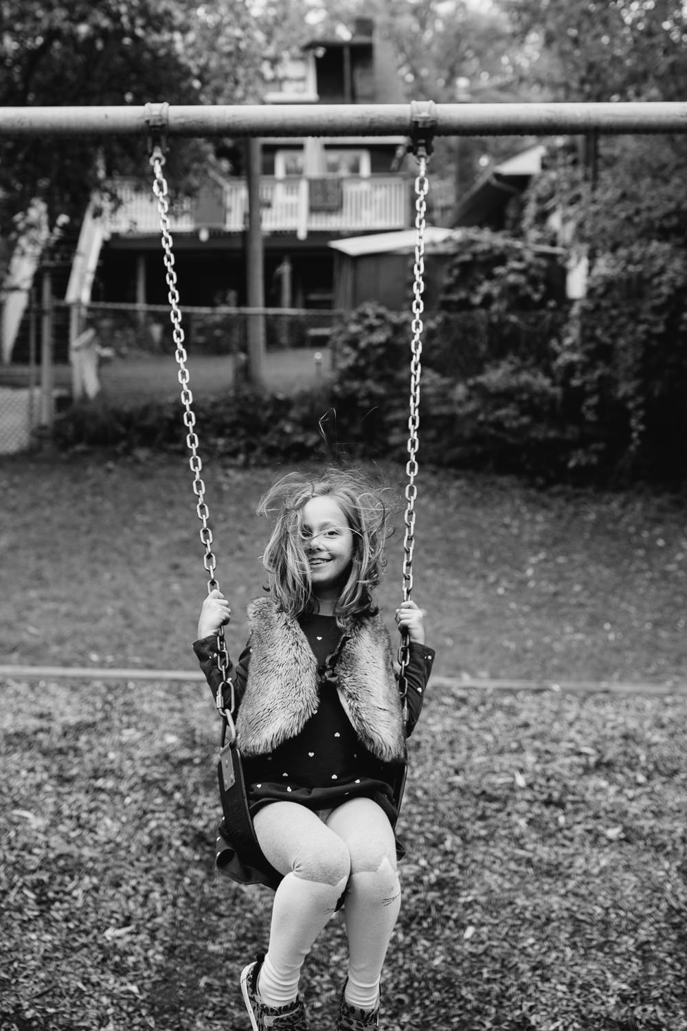 7 year old girl sitting on swing in city park, hair flying in her face as she move backwards, smiling at camera - York Region In-Home Photography
