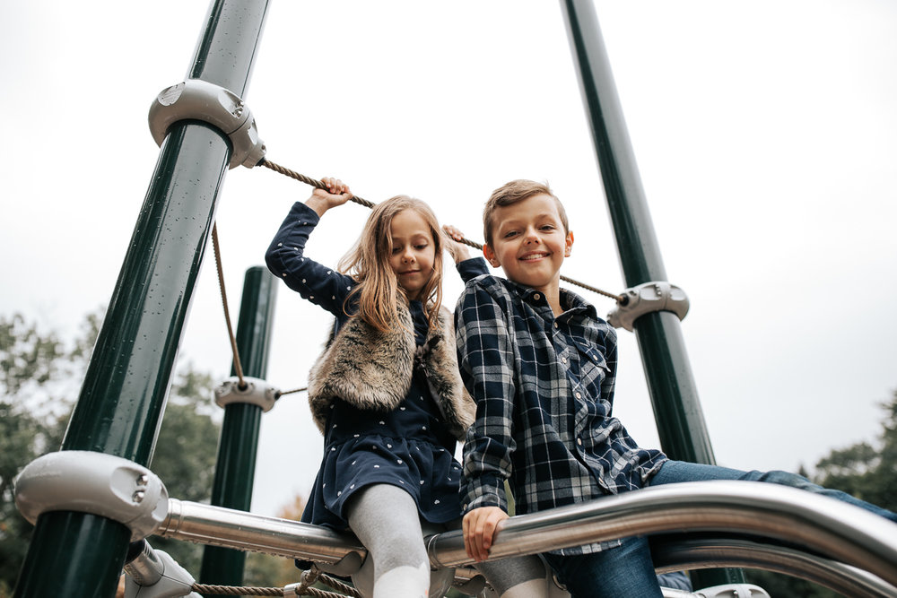 7 year old girl and 9 year old boy sitting on top of jungle gym at city park, brother looking down at camera, sister holding onto rope above head and looking at ground - Barrie In-Home Photos