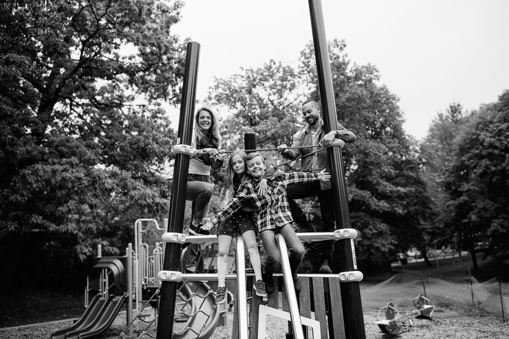 family of 4 standing on jungle gym at city park, 7 year old girl hugging brother, 9 year old boy with arms stretch out, mom and dad standing behind - Newmarket Lifestyle Photos
