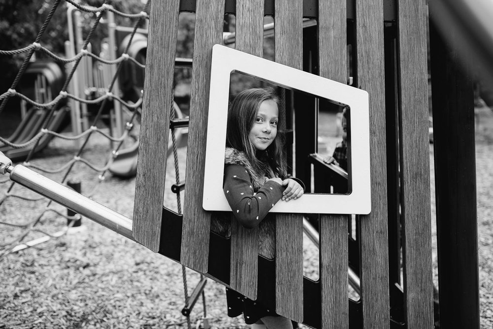 7 year old girl leaning with arm through small window in jungle gym structure at park, looking and smiling softly at camera - Stouffville Lifestyle Photos