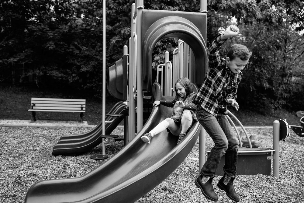 9 year old boy jumping off slide at city park, 7 year old girl sliding down in background - GTA Lifestyle Photos