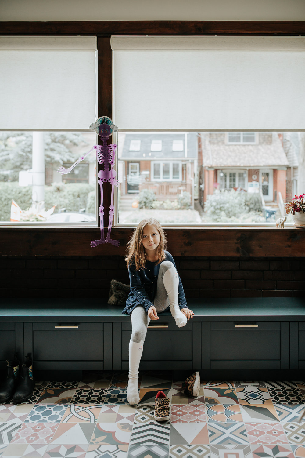 7 year old girl sitting on bench in mudroom, one knee up, taking of shoes after returning from park, looking at camera - Markham Lifestyle Photos
