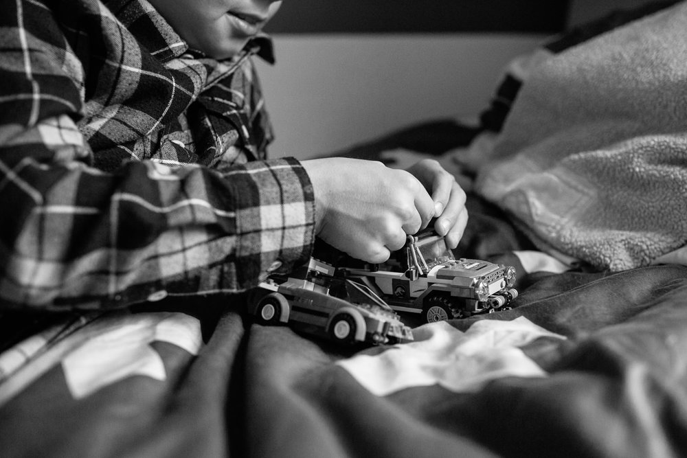 9 year old boy in plaid shirt lying on bed playing with lego, close up of hands - York Region In-Home Photography