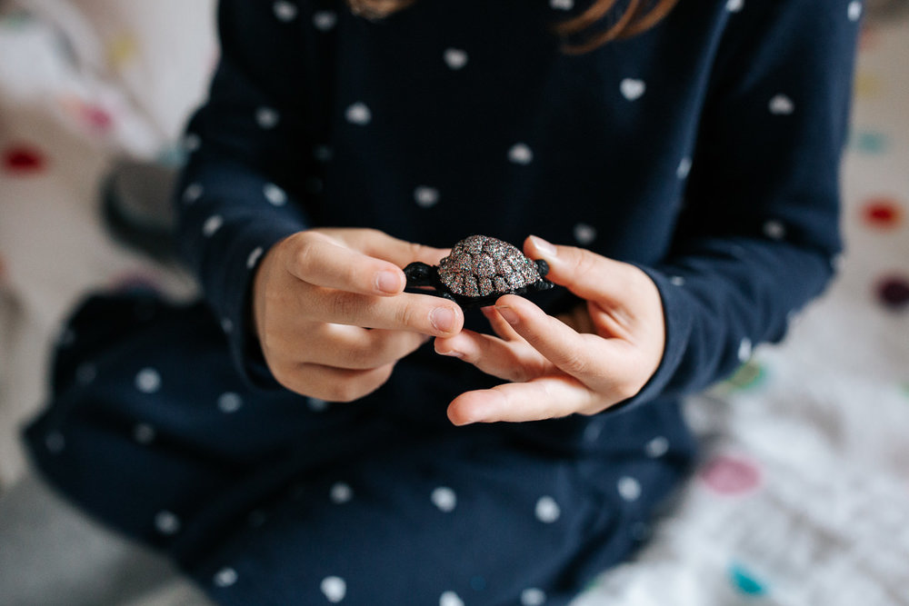 7 year old girl in polka dot dress sitting on bed in her room, holding sparkly turtle toy, close up of hands - Newmarket In-Home Photos
