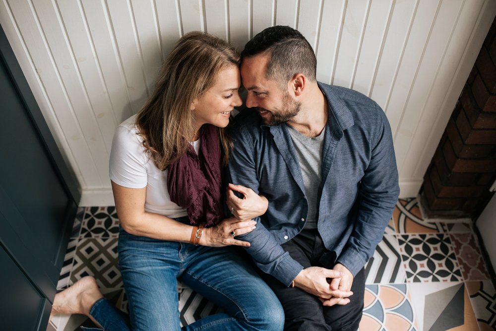 husband and wife sitting on ground of colourful tile, leaning against white wall, arms linked and holding hands, foreheads touching, smiling at one another -  GTA Lifestyle Photos