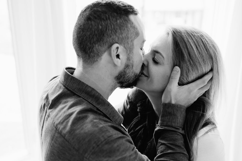 couple standing in front of window, husband's hand's holding wife's face as he kisses her - GTA Lifestyle Photography