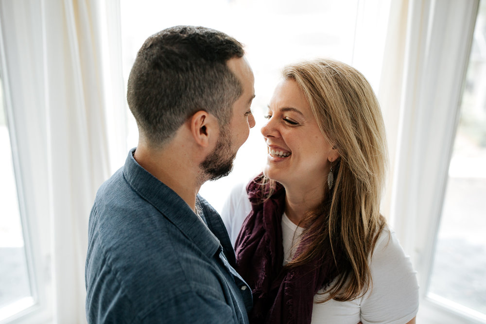couple standing in front of window, wife with blond hair in purple scarf, smiling at husband with dark hair and beard - Barrie Lifestyle Photography