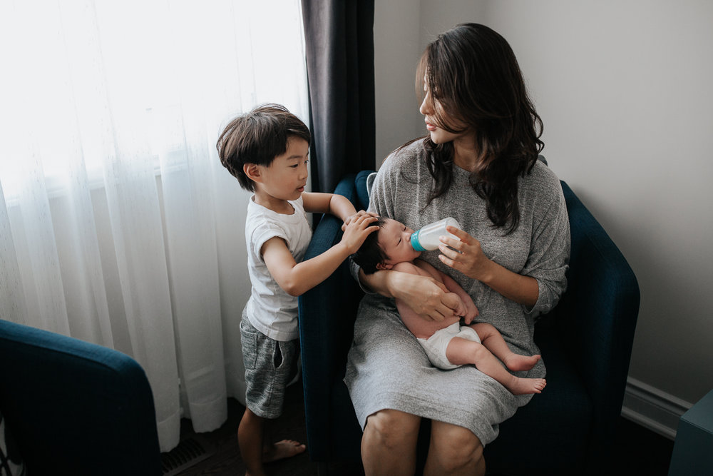 mom with long dark hair sits in blue armchair feeding 2 week old baby boy in diaper a bottle, 3 year old toddler son standing next to her with hands on little brother's head - Markham In-Home Photos