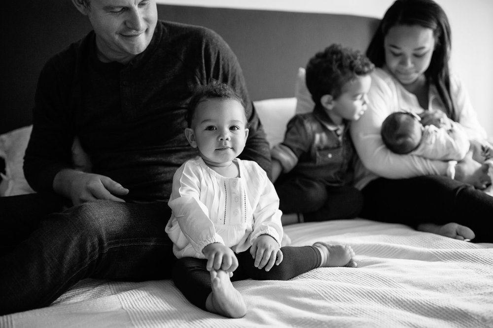 1 year old girl with dark hair and eyes sitting next to dad on master bed looking at camera, mom, brother and baby sister in background - Newmarket Lifestyle Photography