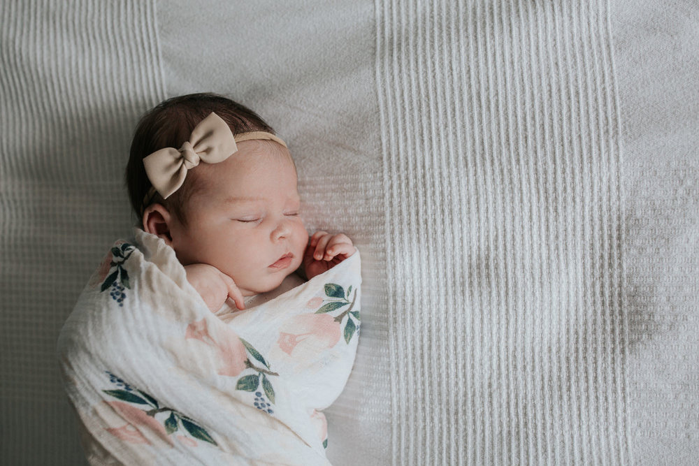 2 week old baby girl with dark hair wrapped in swaddle with soft pink flowers, wearing bow headband asleep on bed, hands near face - Barrie Lifestyle Photography