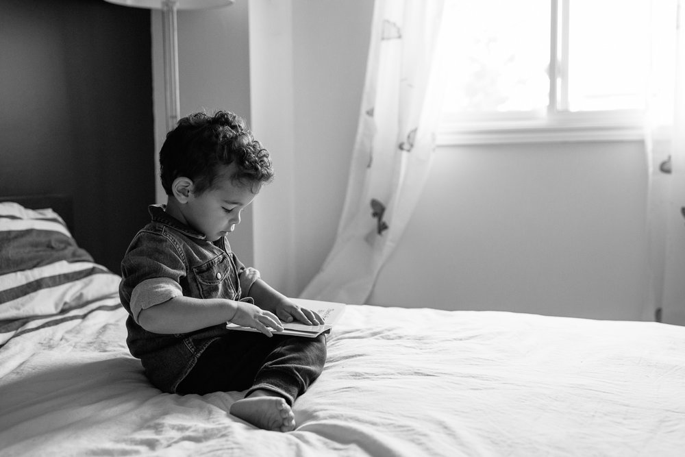 2 year old toddler boy with dark curly hair wearing chambray shirt sitting on his bed reading book - Stouffville Lifestyle Photos
