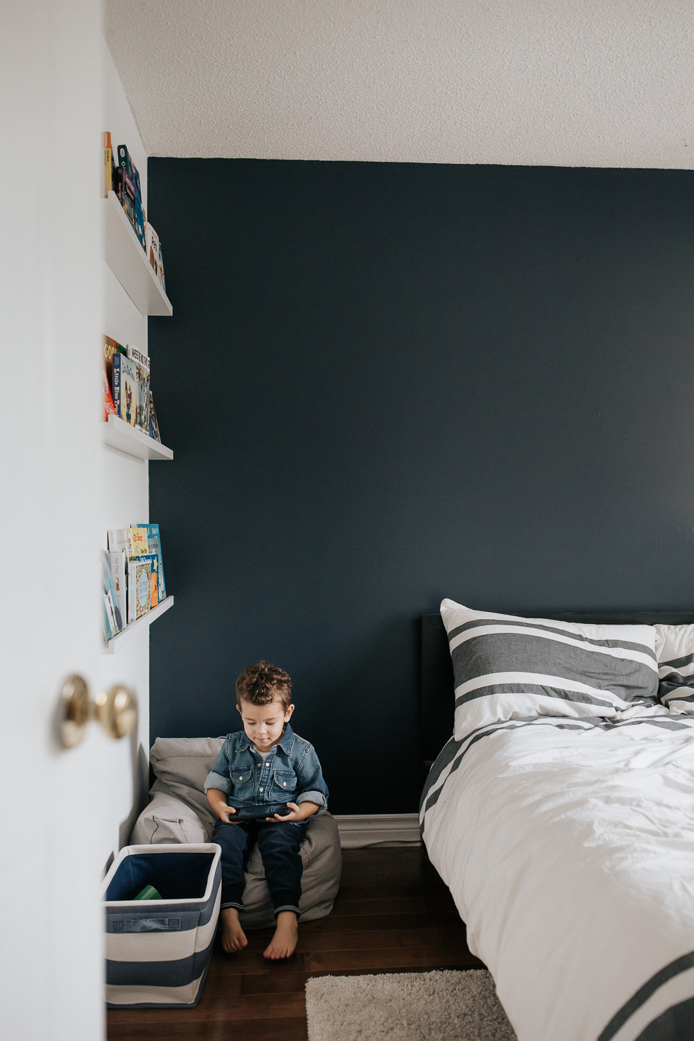 2 year old toddler boy with dark curly hair wearing chambray shirt sitting on chair in corner of his bedroom playing handheld video game - Barrie Lifestyle Photos