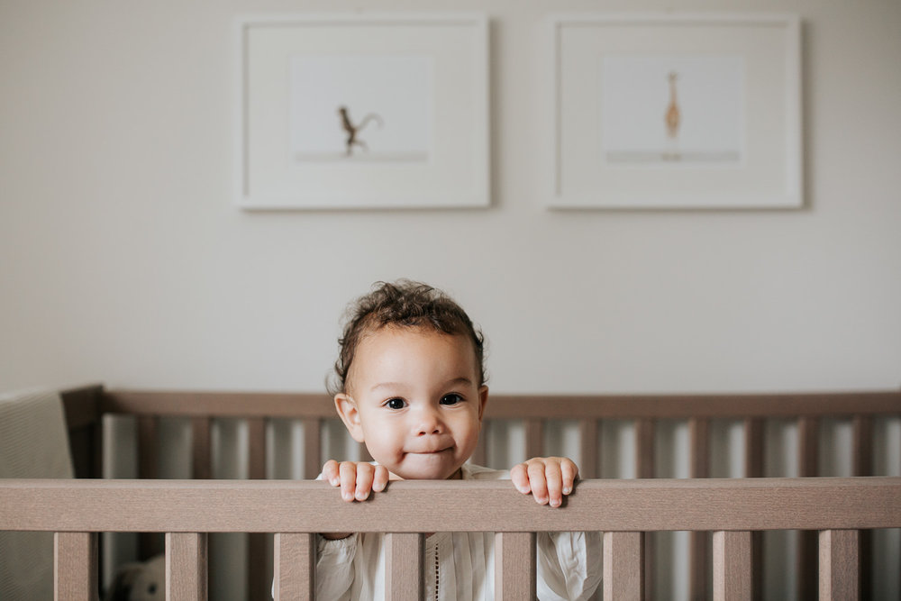 2 year old girl with dark curly hair and brown eyes in cream top and dark pants standing in crib looking at camera in neutral nursery with animal prints on wall - Newmarket Lifestyle Photography