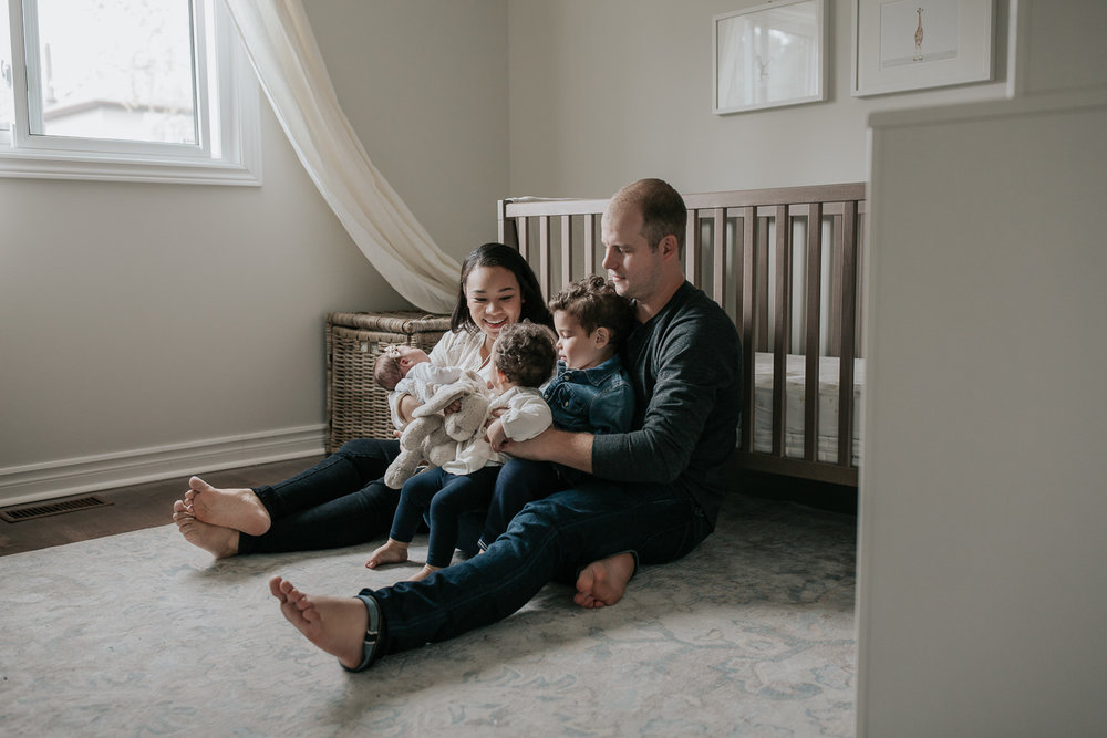 family of 5 sitting on floor of nursery leaning against crib, mom holding 2 week old baby girl, dad snuggling 2 year old boy and 1 year old daughter in his lap - Markham Lifestyle Photos