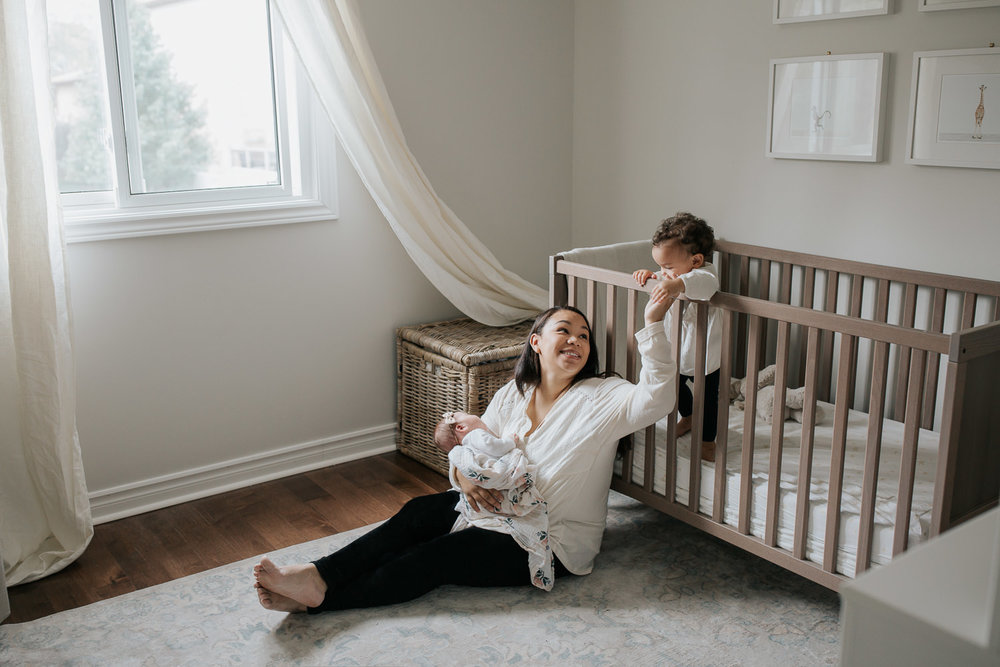 mom with long dark hair sitting on nursery floor holding 2 week old baby girl, smiling and reaching out to 1 year old toddler daughter standing in crib behind her  - Newmarket Lifestyle Photography