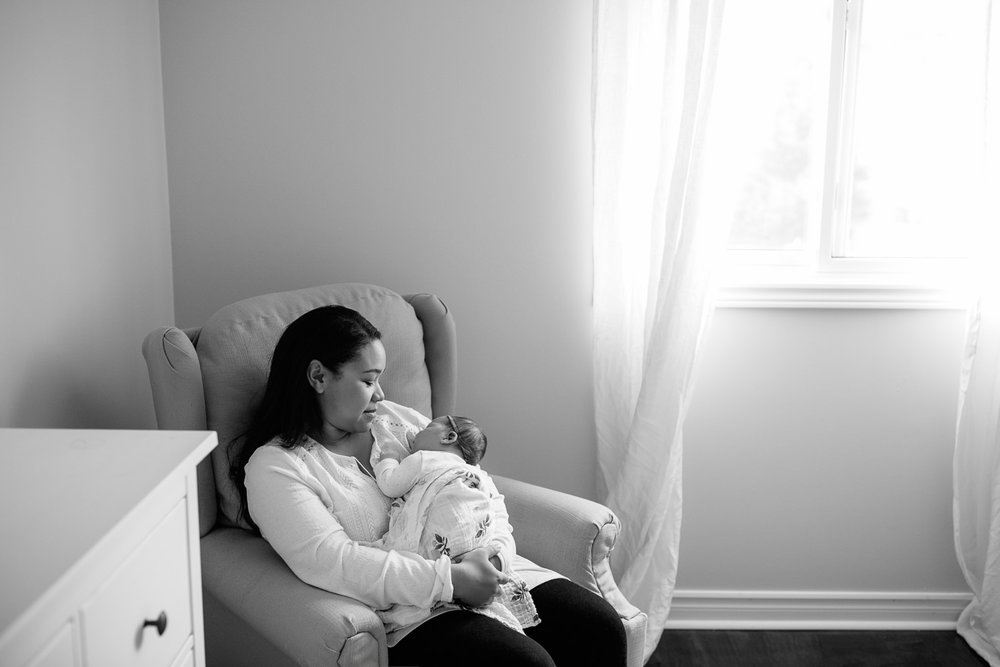 mom with long dark hair in white shirt sitting in nursery glider chair with 2 week old baby girl in onesie and swaddle sleeping on mother's chest - Markham Lifestyle Photography