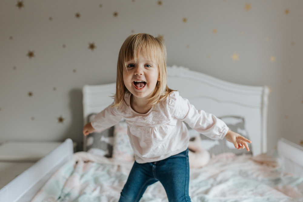 Stouffville In-Home Photography -blonde toddler girl jumping on bed with gold star decals on her wall, toddler bed, happy