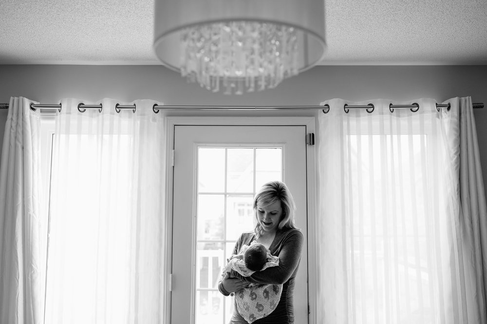 Barrie In-Home Photos - blonde mom adoring her new 2 week old baby boy standing by the door with a crystal chandelier up above