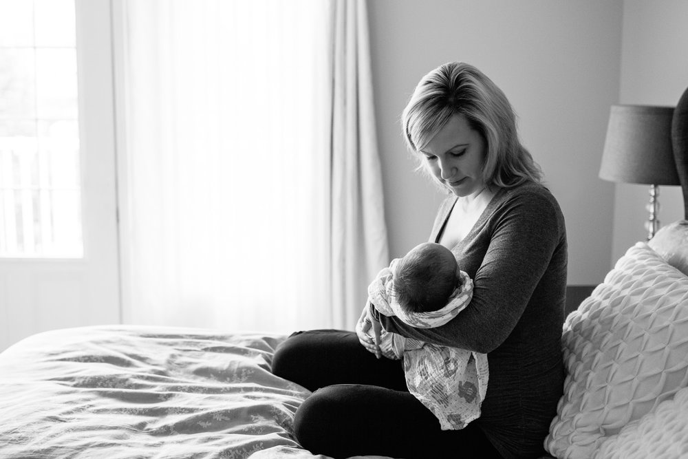 mother sitting on master bed holding 2 week old baby boy in swaddle in her arms, mom looking down at son - Barrie Lifestyle Photos