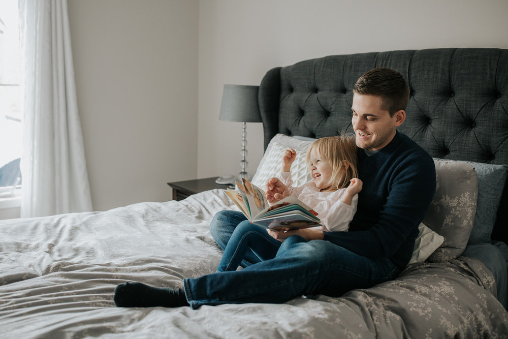 2 year old toddler girl sitting in father's lap on master bed reading a story book, daughter with hands in air laughing - Markham Lifestyle Photos