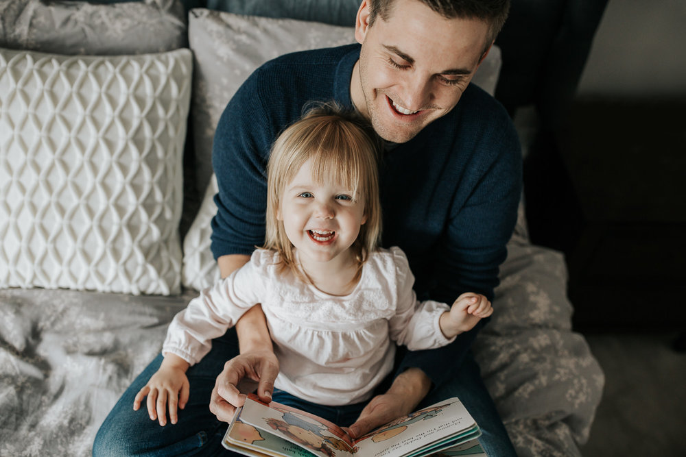 2 year old toddler girl sitting in father's lap on master bed reading a story book, daughter smiling up at camera - Newmarket Lifestyle Photos