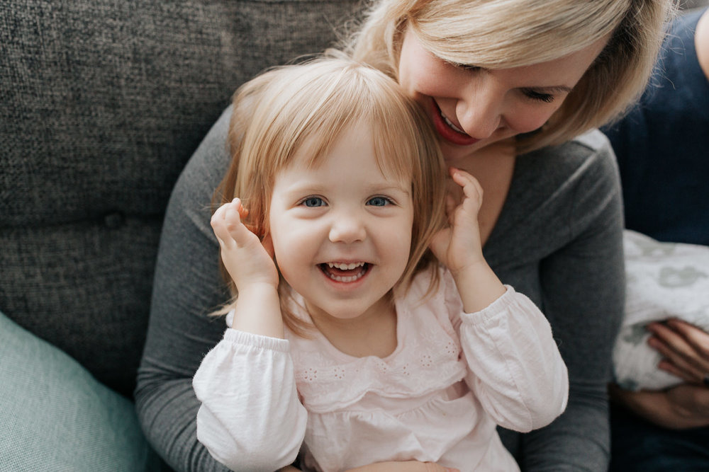 2 year old toddler girl sitting on mom's lap on couch with hands in ears laughing at camera, mother smiling at daughter - GTA Lifestyle Photos