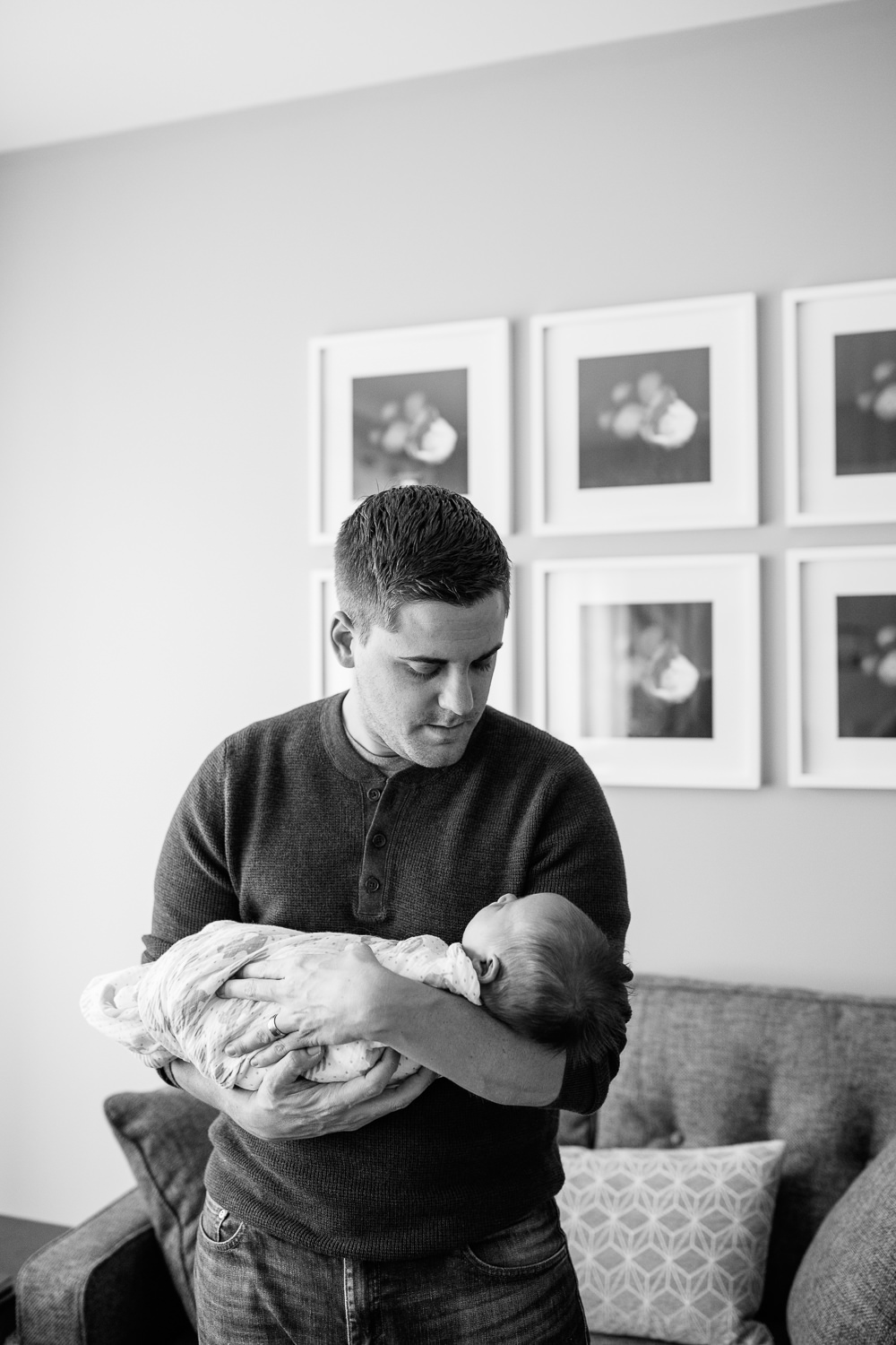 father standing in living room holding sleeping 2 week old baby boy in his arms, looking at son -  Markham Lifestyle Photography
