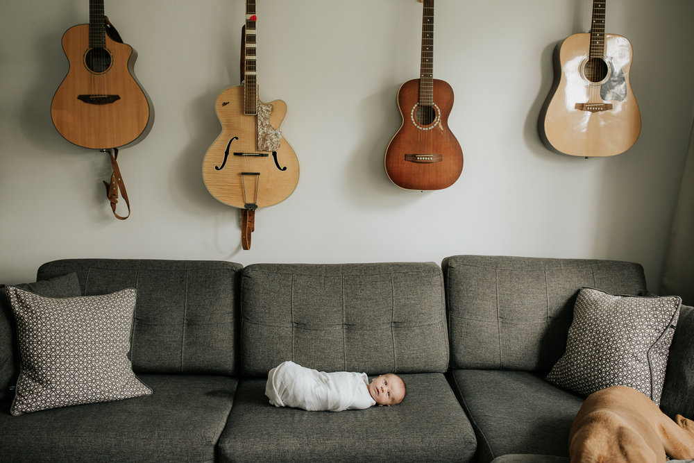 2 week old baby boy in white swaddle lying awake on dark grey couch, guitars hanging on wall above him - Newmarket Lifestyle Photography