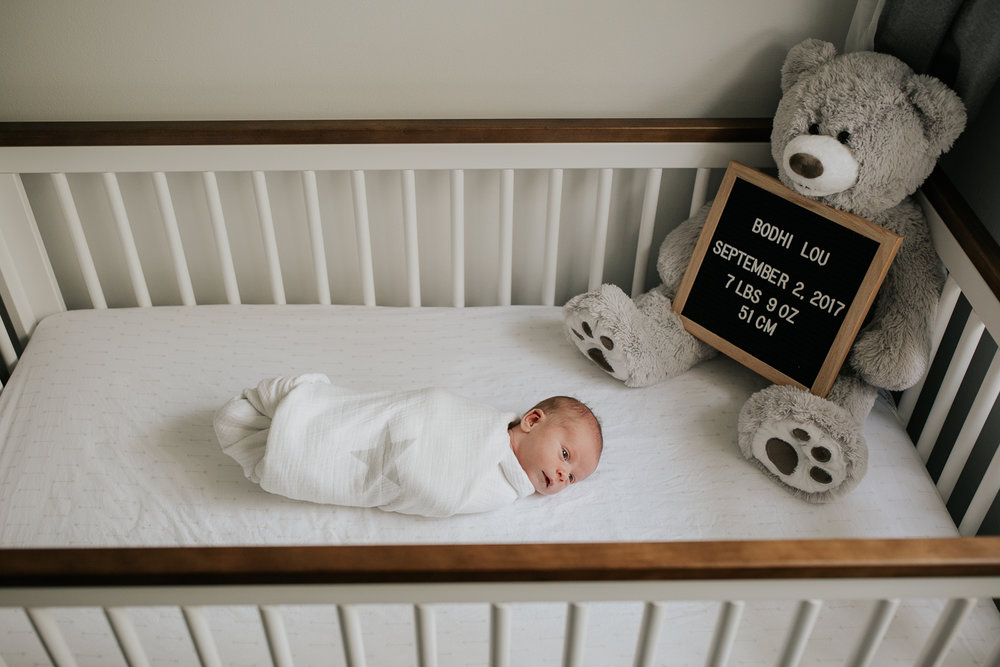 2 week old baby boy in white swaddle with grey stars, lying in white crib with wood trim, awake - GTA In-Home Photography