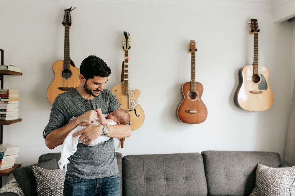 new dad standing in living room in front of wall of guitars, holding 2 week old sleeping baby boy in white swaddle, holding his hands - Barrie Lifestyle Photography