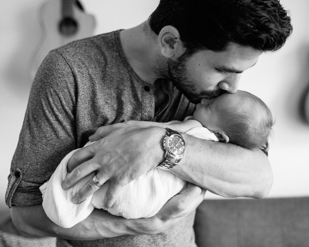new dad standing in living room, holding 2 week old sleeping baby boy in white swaddle, kissing son on forehead - York Region Lifestyle Photography