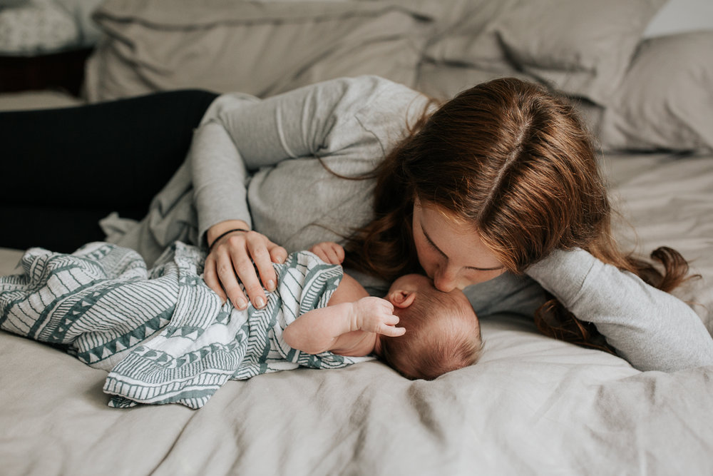 new mom with long red hair lying on bed next to 2 week old baby boy in geometric swaddle, kissing him on forehead - GTA Lifestyle Photography