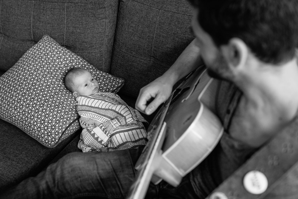 new dad sitting on living room couch playing guitar and singing to 2 week old baby boy lying against cushions watching father - Stouffville In-Home Photography