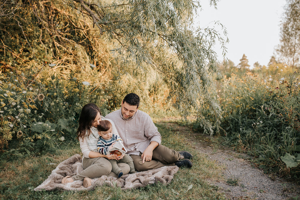 family of 3 sitting on fur blanket under willow tree at sunset, 1 year old baby boy sitting on mom's lap reading story, dad next to them smiling down at son - Barrie Lifestyle Photography
