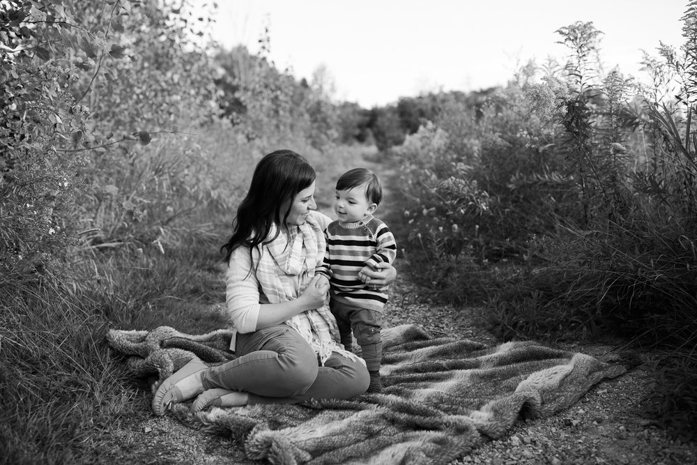 mother sitting on fur blanket on outdoor grassy path, 1 year old baby boy standing next to her, mom and son smiling at each other - GTA Golden Hour Photography