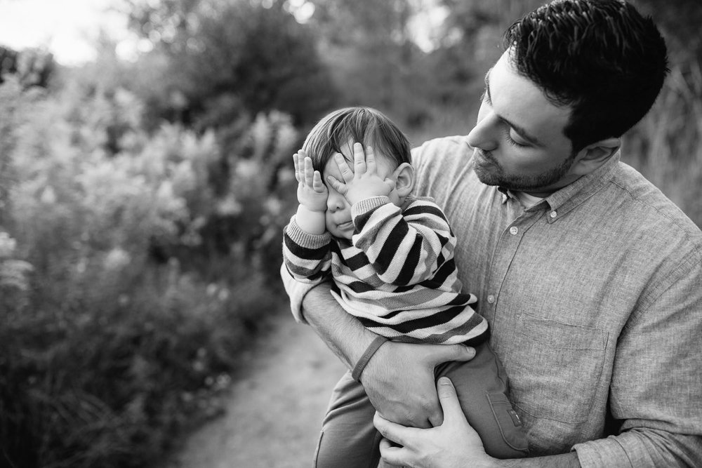 dad standing in golden field holding 1 year old baby boy, child with hands over eyes playing peek-a-boo, father smiling at son - Newmarket Lifestyle Photography
