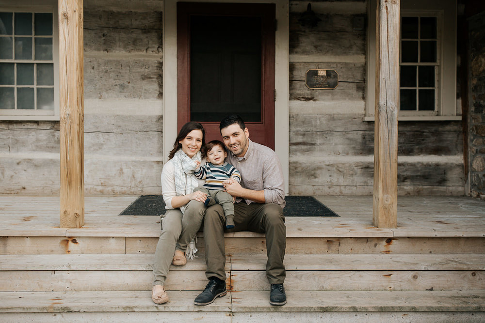 family of 3 sitting on front porch steps of historic log cabin, son on dad's lap, mom next to them, smiling at camera - Stouffville Outdoor Photography