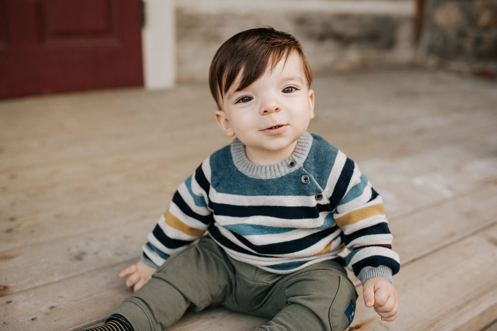 1 year old baby boy with brown hair and eyes in striped sweater sitting on front porch, looking at camera - Newmarket Outdoor Photography