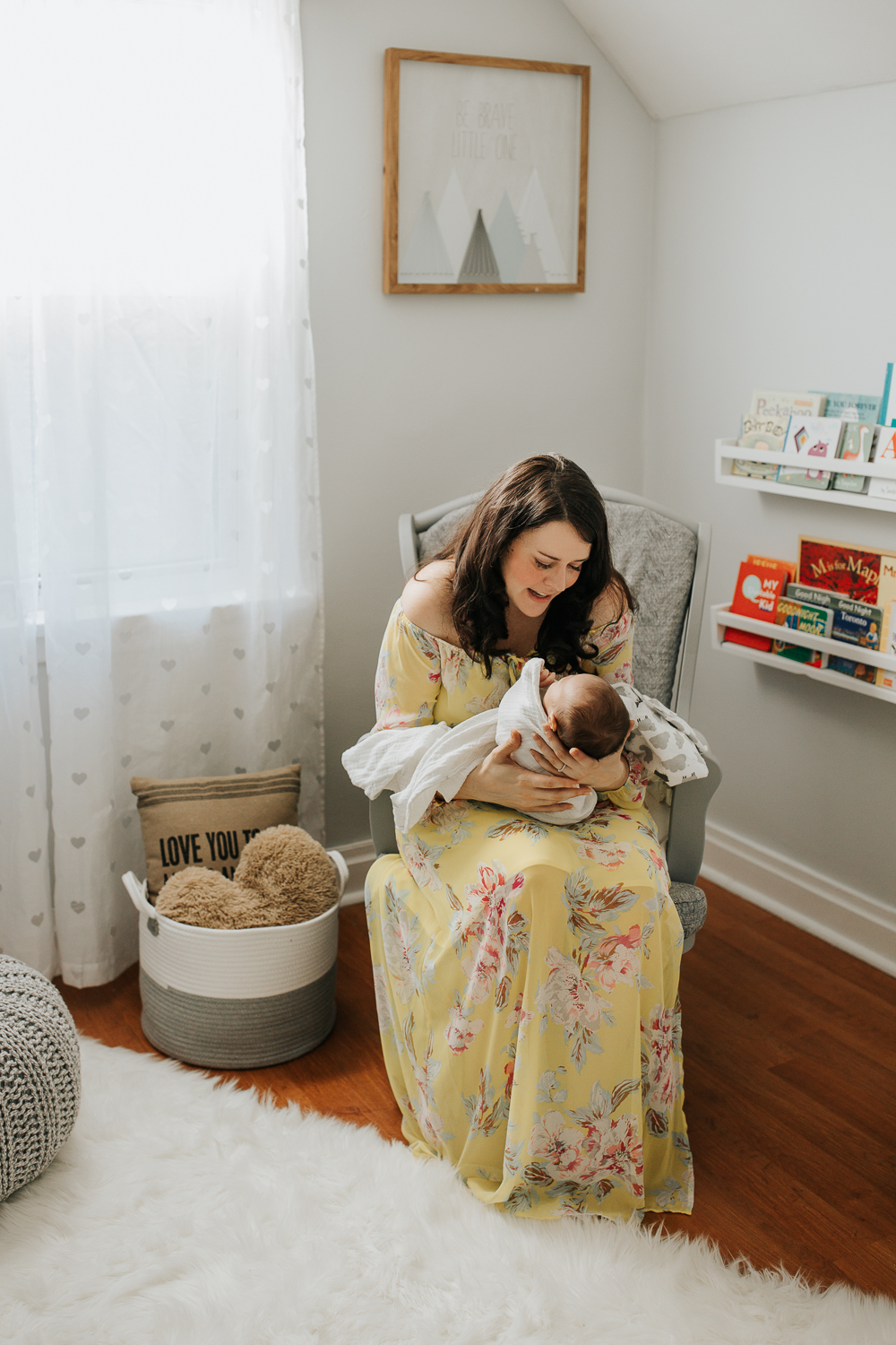new mother sitting in nursery rocker, 2 week old baby boy lying in her arms, mom smiling at son - Barrie Lifestyle Photography